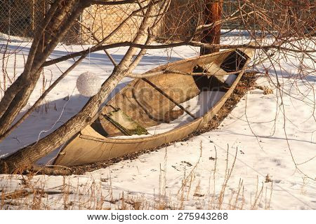 A Old Abandoned Wood Canoe By A Frozen Pond.