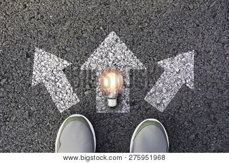 Shoes Standing  And Light Bulb At The Crossroad And Get To Decision Which Way To Go. Ways To Choose