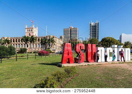 Asuncion, Paraguay - July 13, 2018: Five Tourists Are Posing With Asuncion Letters And Palacio De Lo