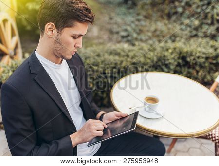 Smart Business Man Using His Tablet While Having Breakfast At Coffee Shop, Businessman Holding Cup O
