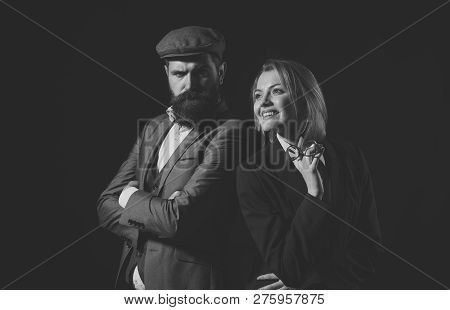 Man and woman in oldfashioned suit and hat on black background. Retro detective concept. Couple of detectives or researchers, private investigators. Couple in love or work partners working together. poster