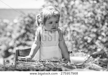 Cute Little Boy In White Pinafore Sits In High Chair At Table With Cup Of Milk On Sunny Summer Day O