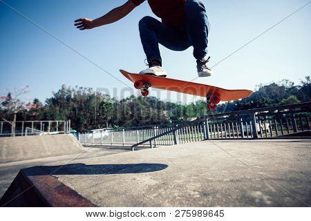 One Skateboarder Skateboarding Jumping At Skatepark Ramp