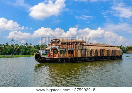 A Beautiful Houseboat Sailing Through The Backwaters In Kerala, India On A Sunny Day, With Clear Blu
