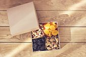 A box of nuts and dried fruits on old wooden background. hazelnut, cashew, dried daddy, dried apricots, prunes, dried pineapple. Gift box with bow poster