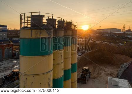 Silos For Storage Of Cement Aerial View. Evening Shooting, The Setting Sun. Silos Are Painted In Yel