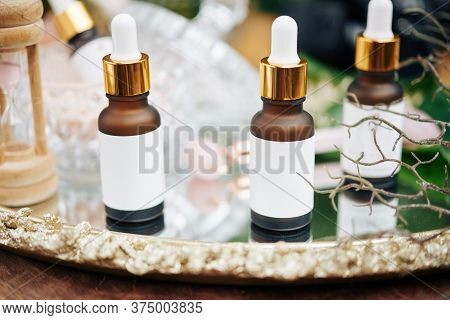 Small Bottles With Hydrating, Brightening And Anti-aging Serums And Essentials On Beautiful Metal Tr