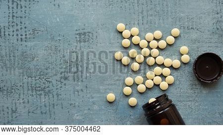 Yellow Round Tablets Or Pills Vitamins On Blue Stone Concrete Table With Black Plastic Bottle, Side