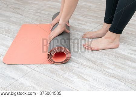Woman Rolling Her Mat After A Yoga Class On A Wooden Floor At Home. Girl Doing Yoga Exercises