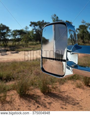 Car Side Mirror Reflecting A Blurred Vision Of A Caravan Traveling On A Dirt Road In The Australian