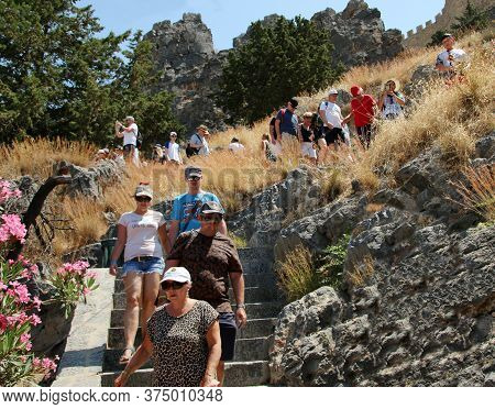 Lindos, Rhodes, Greece - August 29, 2019: Tourists On The Path Descending From The Top Of The Acropo