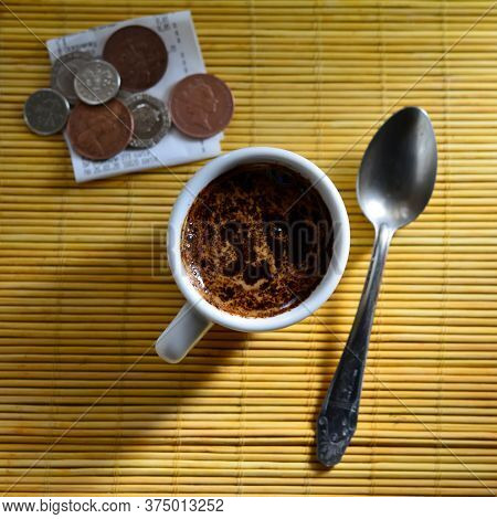 Check And Coins With A Cup Of Coffee And A Spoon Lie On A Table In A Cafe. Web Banner. Business Conc