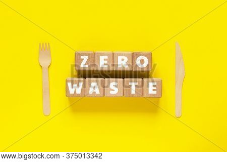 Wood Cubes With Text Zero Waste, Wooden Fork And Knife On Yellow Background. Eco-friendly Disposable