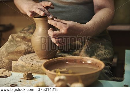 Process Of Making Clay Pot On A Potters Wheel In Workshop. Potter At Work