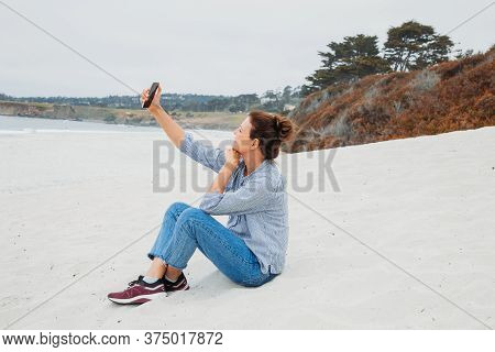 Happy Stylish Middle Age Woman Taking Selfie With Mobile Phone On A White Beach.