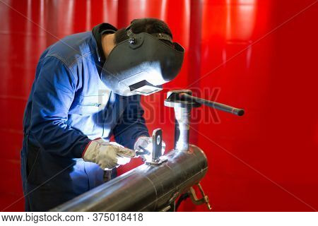 Welder at work in a production facility, man welding an iron or steel pipe