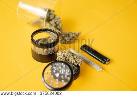 Yellow Background. Cannabis Weed Bud And Grinder. The Pot Leaves On Buds. Thc Cbd. Joint Weed.