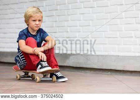 Looking Unhappy And Upset Skater Sit On Skateboard Before Children Training Class In Skate Park. Act