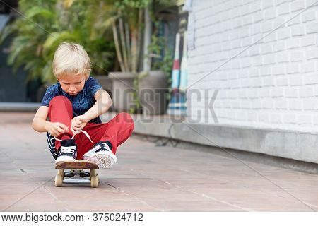 Little Skateboarder Sit On Skateboard Tying Shoelaces Before Children Training Class In Park. Active