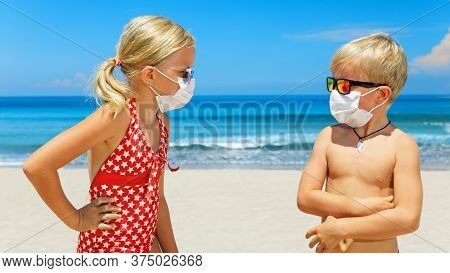 Two Young Funny Children Wearing Sunglasses, Protective Mask On Sea Beach. Summer Tours, Cruises Can