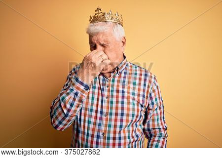 Senior handsome hoary man wearing golden crown of king over isolated yellow background smelling something stinky and disgusting, intolerable smell, holding breath with fingers on nose. Bad smell