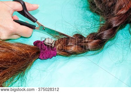 A Woman's Hand With A Pair Of Scissors Cuts A Long Plait Of Dark Hair. Close-up, Turquoise Backgroun