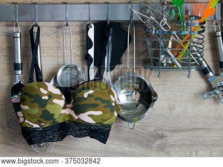 It Is Important To Wear A Bra At Home As Well.an Army-style Bra Hangs Between Utensils In The Kitche