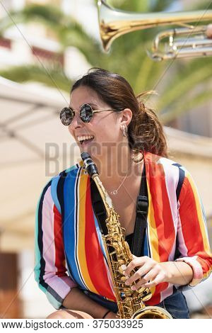 Happy Young Woman Wearing Glasses And Holding A Golden Saxophone. Street Music And Lifestyle Concept