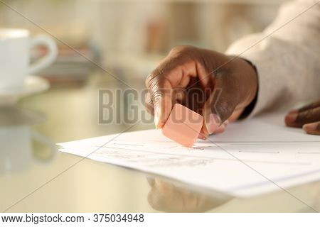 Close Up Of Black Man Hands Erasing With Rubber Sitting On A Desk At Home