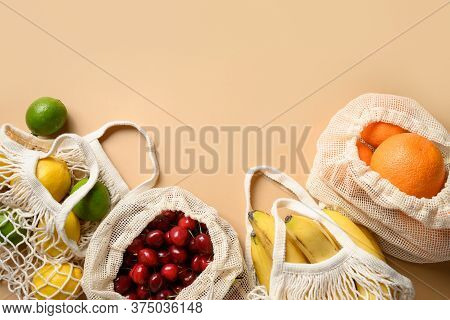 Fruits, Berries And Citrics In Mesh Bags On Beige Background. Zero Waste Shopping. Ecological Concep