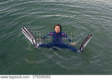 Beach Vacation Fun Woman Wearing A Wetsuit And Flippers Making A Goofy Face While Swimming In Ocean