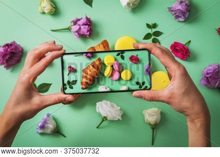 Food Blog - Blogger Taking Picture Of Macarons And Croissant With Phone