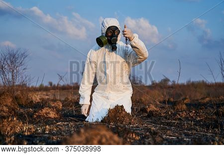 Male Environmentalist In Suit And Gas Mask Pouring Out Soil From His Hand While Doing Research Work