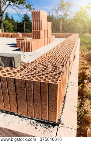 Construction Site Of A Family House. Concrete Base Plate. Wall Construction. Red Bricks On A Constru