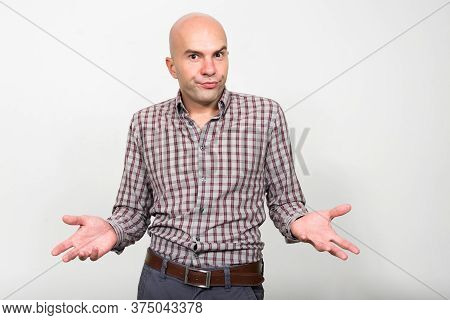 Portrait Of Bald Businessman Shrugging Shoulders And Looking Confused
