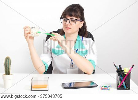 Beautiful Caucasian Woman Doctor With Glasses Holds A Mock Toothbrush And A Toothbrush In Her Hands.