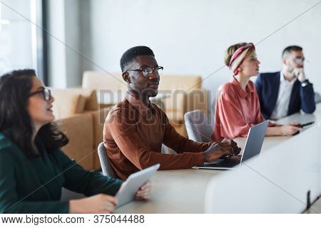 Multi-ethnic Group Of Young Business People Sitting At Table In Conference Room During Training Semi