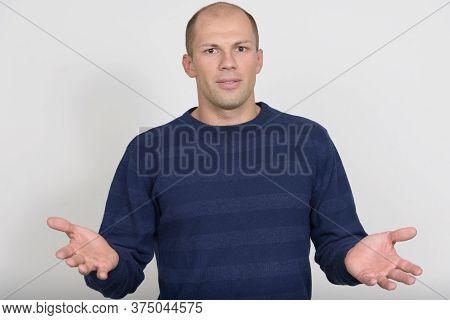 Portrait Of Young Handsome Bald Man Shrugging Shoulders