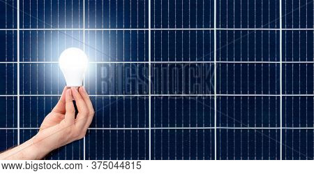 Hand Holding White Bulb Against Solar Panel, Solar Station. Idea Concept Of Alternative Energy, Tech