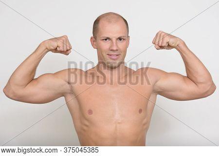 Happy Young Muscular Bald Man Flexing Both Arms Shirtless