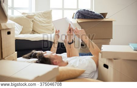Cute couple unpacking cardboard boxes in their new home, lying on the floor and looking at a family album