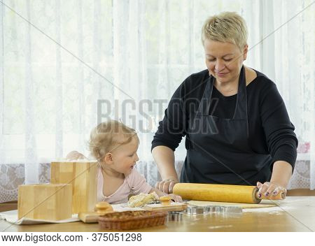Happy Grandma And Granddaughter On Kitchen. Beautiful Grandmother And Cute Playful Baby Having Fun W