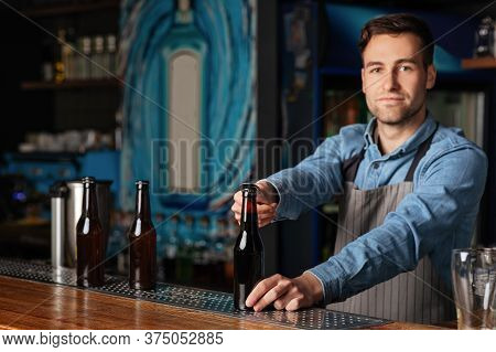 Serve Customers At Bar. Serious Handsome Barman In Apron Opens Bottle Of Beer In Interior Of Modern
