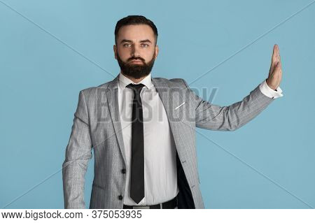 Serious Office Employee Showing Stop Gesture, Expressing Denial Against Blue Background