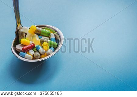 Spoon With Pills Isolated On Blue Background. Colorful Capsules And Pills. Pharmacy Drug Assortment