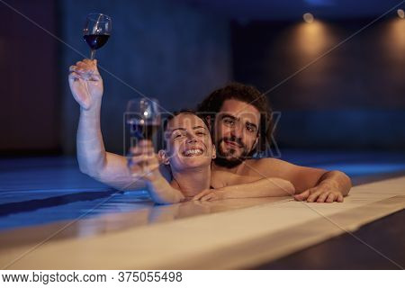 Couple In Love Enjoying Their Vacation, Relaxing In The Spa Center Swimming Pool, Drinking Wine And