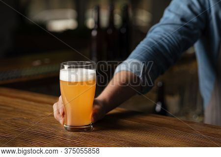 Pint Of Beer In Trendy Bar. Bartender Puts Glass Of Light Beer With Foam On Wooden Table, In Interio