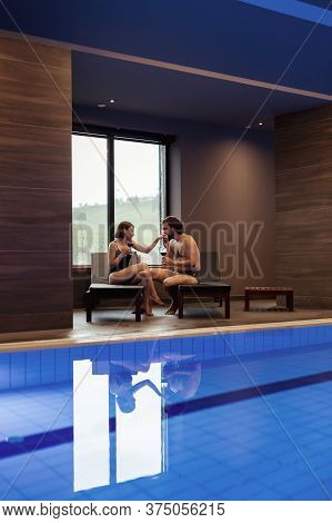 Couple In Love Enjoying Their Vacation, Sitting On Sunbeds By The Spa Center Swimming Pool, Relaxing