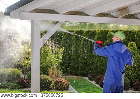 Caucasian Men In His 30s Pressure Washing Garden Porch Wooden Roof Which Get Dirty During Winter Sea