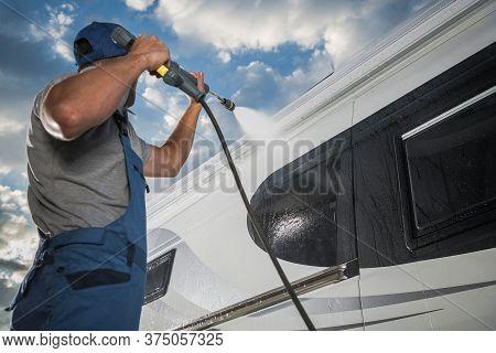 Caucasian Men Pressure Washing His Modern Camper Van Rv Class B. Recreational Vehicle Maintenance. K